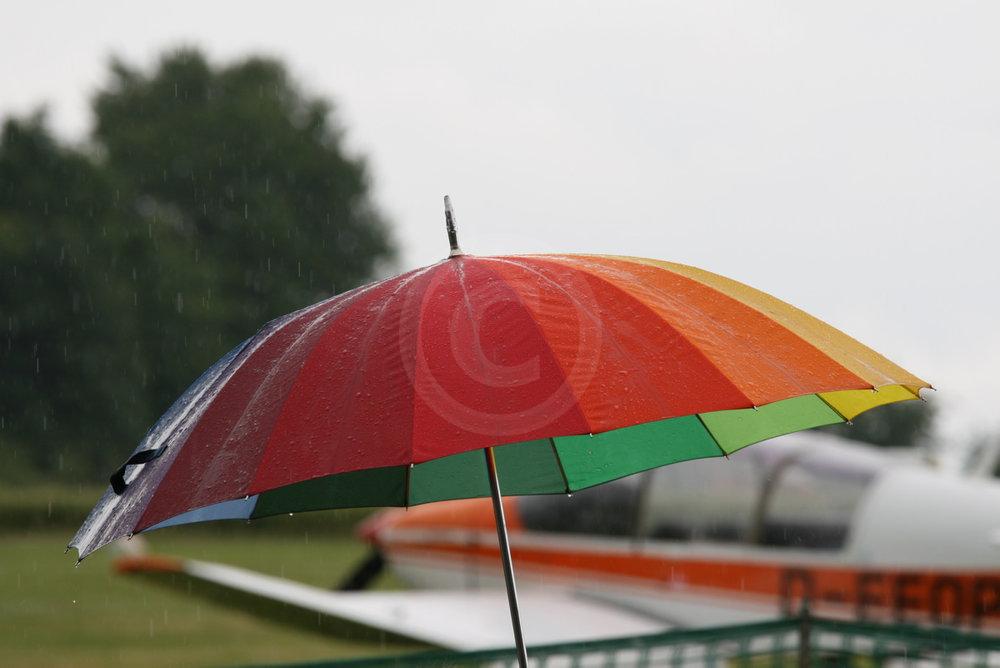 bunter Regenschirm beim Flugtag, im Hintergrund Flugzeuge   - weiter zur Fotogalerie